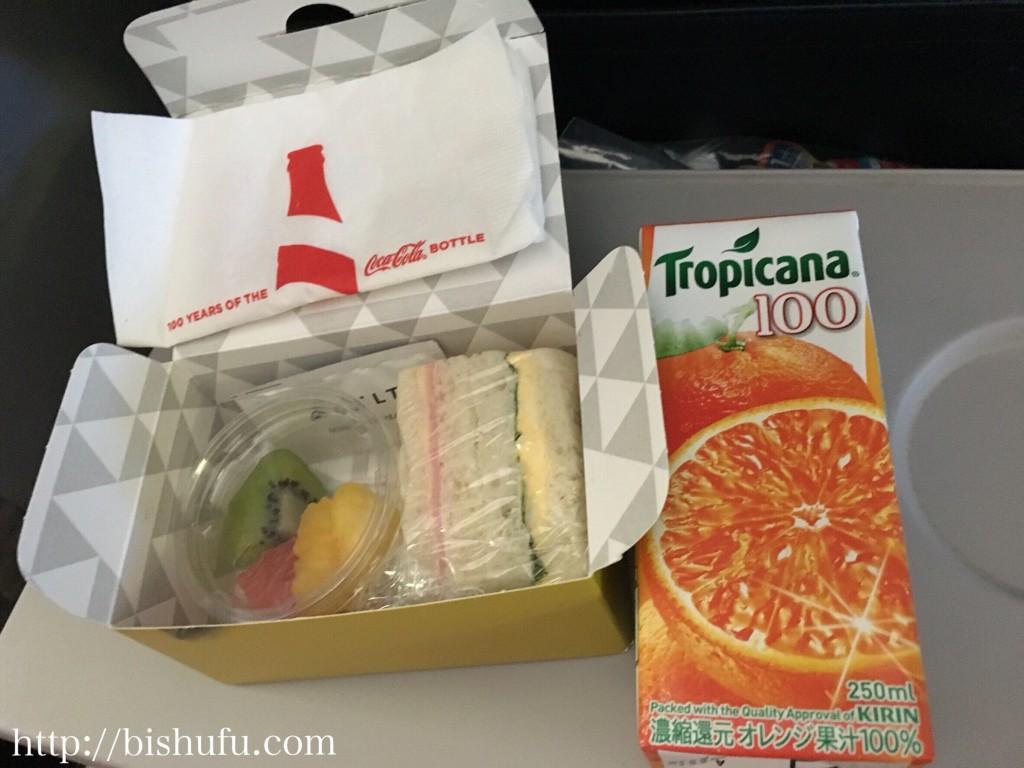 デルタ航空の軽食のハムとたまごのサンドウィッチ、フルーツ、オレンジジュース
